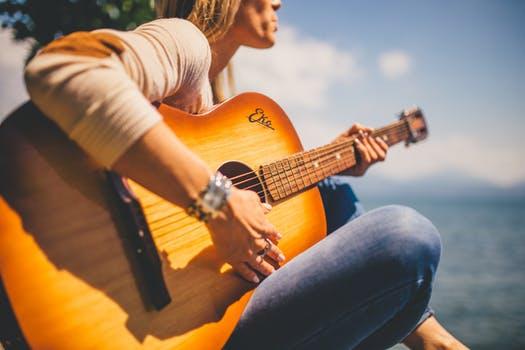 wanita sedang memainkan gitar akustik